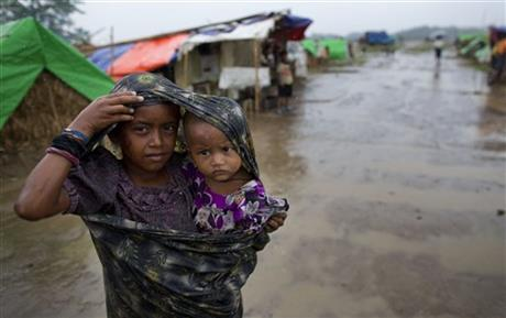 A young Rohingya girl and her sibling brace for Cyclone Mahasen in an IDP camp in Rakhine state (courtesy of The Los Angeles Times).