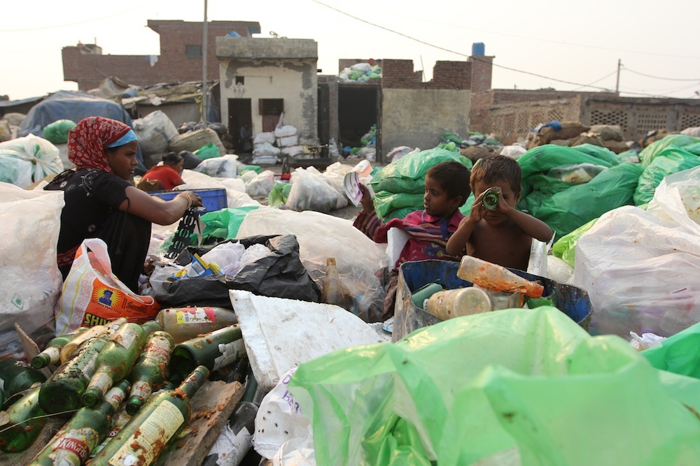 "Two young Indian boys play with items they found in a garbage pile, while their mother sorts through the waste. In India, people who sort and sell trash for a living - an incredibly important job in a country with poor solid waste management - are overwhelmingly from low castes and are commonly known as ""ragpickers"" (courtesy of Don't Waste People)."
