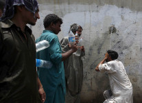 A man (R) cools off under a public tap, while others wait to fill their bottles, during intense hot weather in Karachi, Pakistan, June 23, 2015. A devastating heat wave has killed more than 400 people in Pakistan's southern city of Karachi over the past three days, health officials said on Tuesday, as paramilitaries set up emergency medical camps in the streets. REUTERS/Akhtar Soomro       - RTX1HPUL